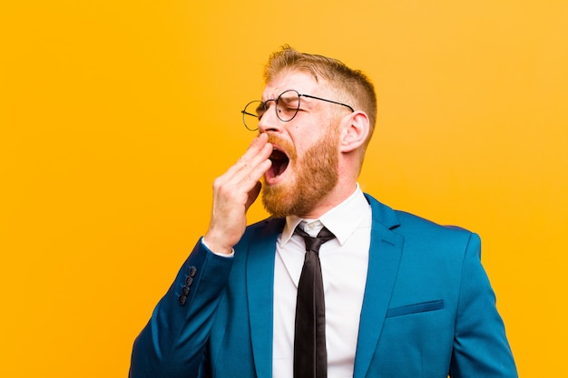 Young red head businessman yawning lazily early in the morning, waking and looking sleepy, tired and bored