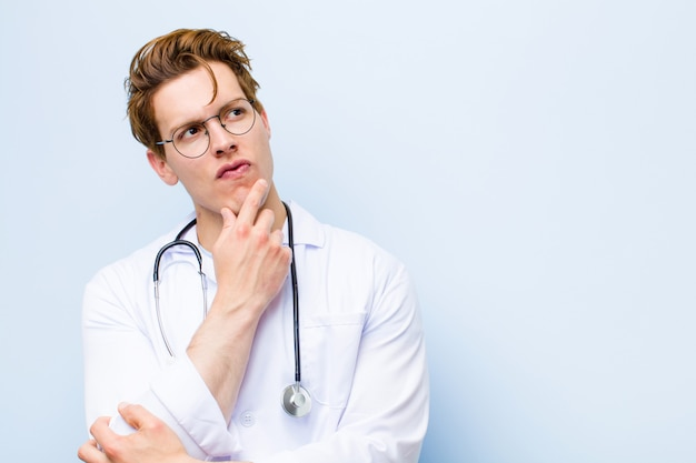 Young red head doctor thinking, feeling doubtful and confused, with different options, wondering which decision to make on blue wall