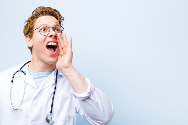 Young red head doctor yelling loudly and angrily to copy space on the side, with hand next to mouth against blue wall