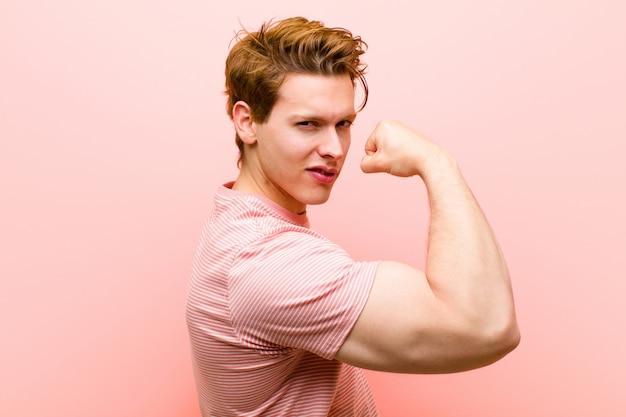 ピンクの壁に対してジムの後に強く見える、幸せ、満足、そして力強い、しなやかなフィット感と上腕二頭筋を感じている若い赤い頭の男
