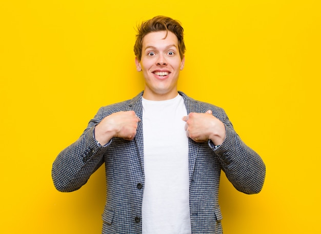 Young red head man feeling happy, surprised and proud, pointing to self with an excited, amazed look against orange background