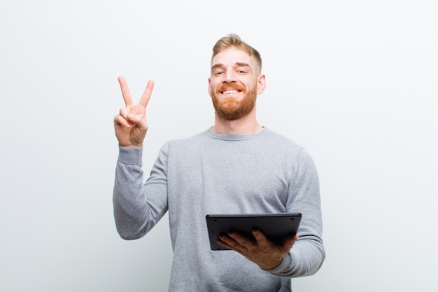 Young red head man holding a tablet against white background
