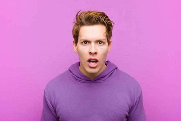 非常にショックを受けた、または驚いて、口を開けて紫の壁に「すごい」と言って見つめている若い赤い頭の男