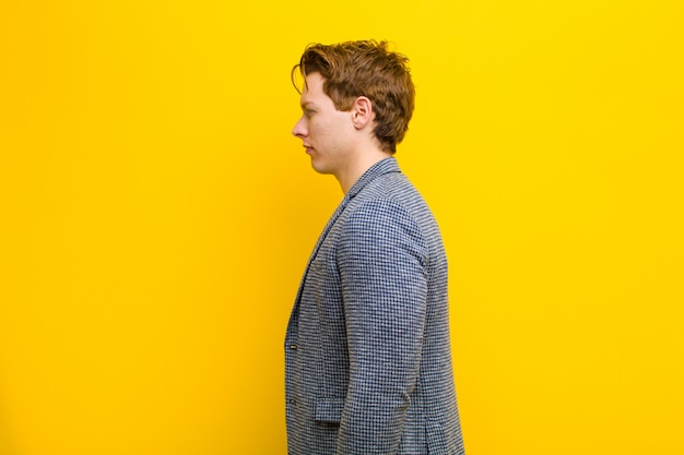 Young red head man on profile view looking to copy space ahead, thinking, imagining or daydreaming on orange