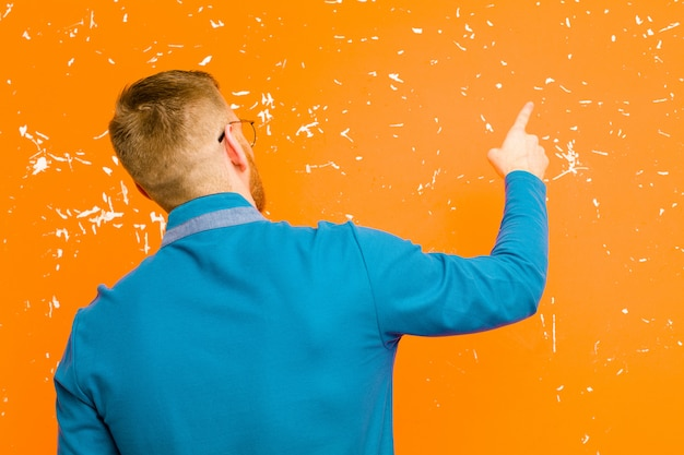 Young red head man standing and pointing to object on copy space, rear view against grunge orange wall