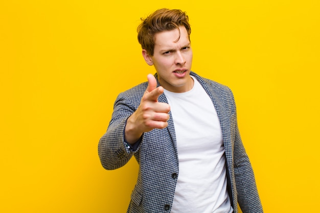 Young red head man with an angry aggressive expression looking like a furious, crazy boss against orange wall