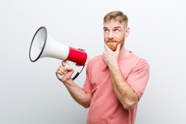 Young red head man with a megaphone against white
