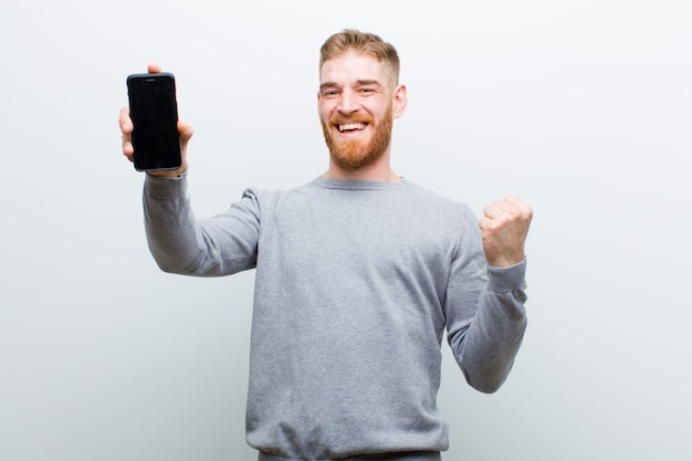Young red head man with a smart phone against white background
