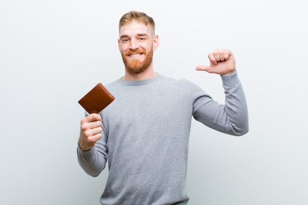 Young red head man with a wallet   white wall
