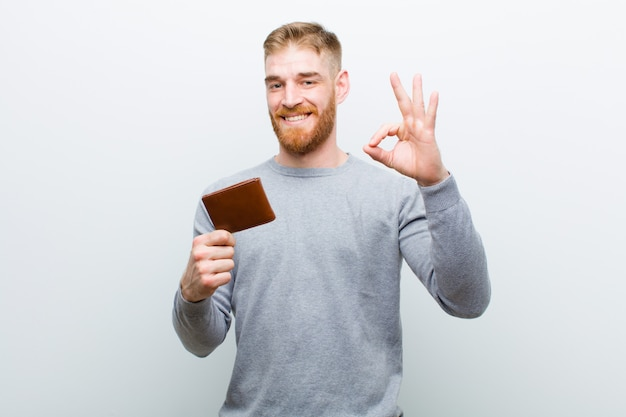 Young red head man with a wallet on white