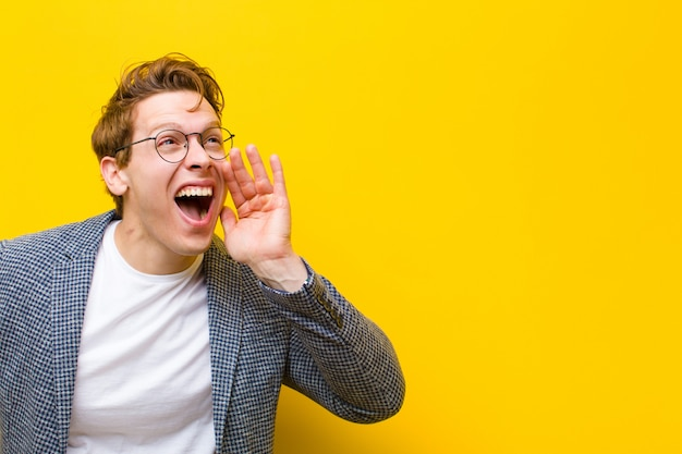 Young red head man yelling loudly and angrily to copyspace on the side, with hand next to mouth  orange
