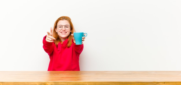 Young red head pretty woman in front of a wooden table with a coffee cup