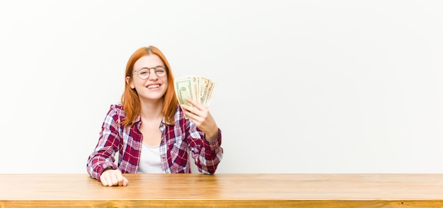 Young red head pretty woman in front of a wooden table with dollar banknotes