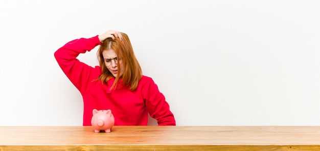 Young red head pretty woman in front of a wooden table with a piggy bank