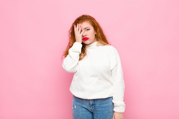 Young red head woman feeling bored, frustrated and sleepy after a tiresome, dull and tedious task, holding face with hand over pink wall