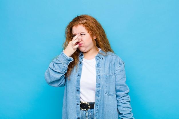 파란 벽에 파울과 불쾌한 악취를 피하기 위해 코를 잡고 젊은 빨간 머리 여자 혐오 느낌