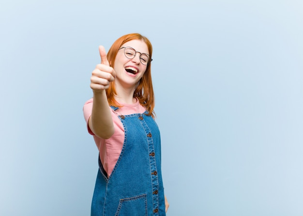 Young red head woman feeling proud, carefree, confident and happy, smiling positively with thumbs up