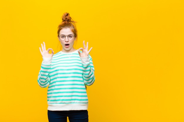 Young red head woman feeling shocked, amazed and surprised, showing approval making okay sign with both hands on orange wall