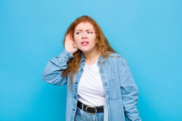 Молодая рыжеволосая женщина ищет серьезного и любопытного, слушает, пытается услышать секретный разговор или сплетни, подслушивая против голубой стены