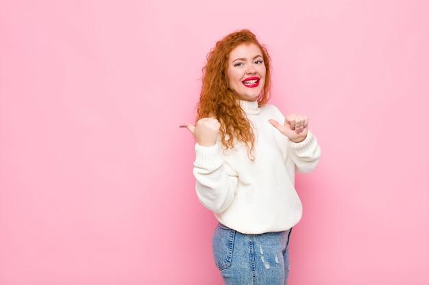 若い赤頭の女性が明るく、さりげなく側のコピースペースを指して笑って、ピンクの壁に満足して満足