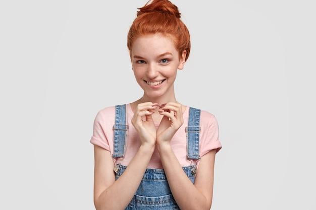 デニムのオーバーオールの若い赤毛の女性