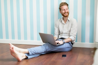 Young redhair man sitting on the floor and working on laptop