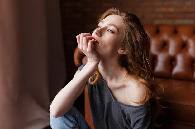 Giovane ritratto della donna del redhair che si siede sul sofà di cuoio marrone.