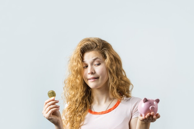 Young redhaired curly girl over white background holding piggy bank and rejoices gesturing