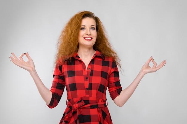 Молодая рыжеволосая девушка в красной клетчатой рубашке.
