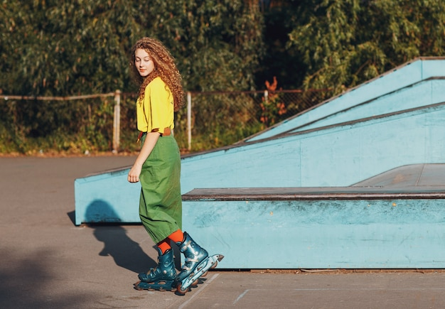 Молодая рыжеволосая женщина в зелено-желтой одежде и оранжевых чулках с фигурной прической катается на роликовых коньках в скейт-роллер-парке
