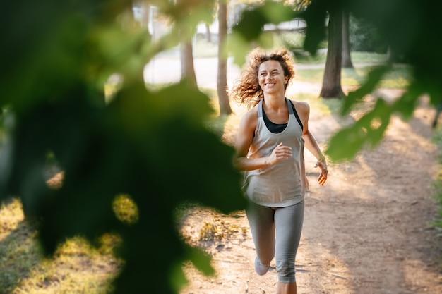 Молодая рыжеволосая женщина пробегает марафон на открытом воздухе в городском парке в лесу в теплых лучах солнца