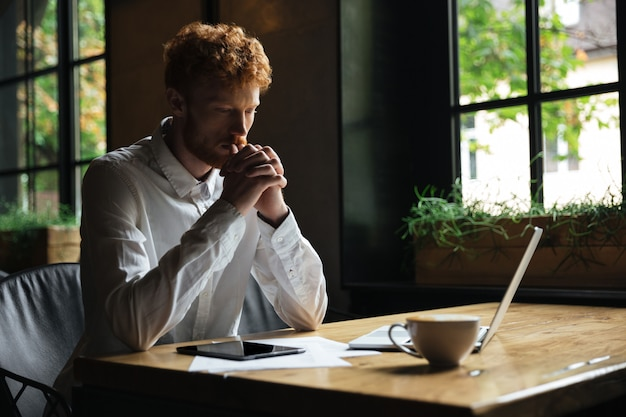 Young redhead bearded man holding hands together and thinking while sitting in the cafe