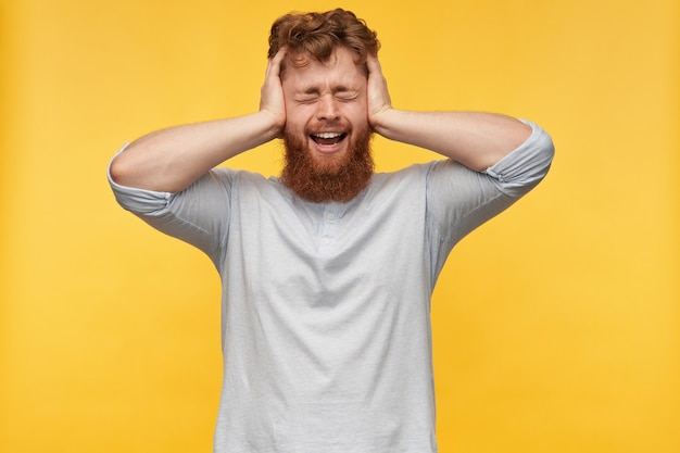 Young redhead bearded man with, keeps his eyes closed, holding head with both hands, screaming while feels pain on yellow.