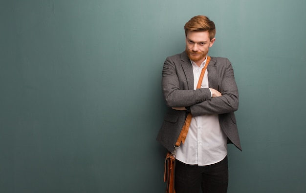 Young redhead business man crossing arms relaxed