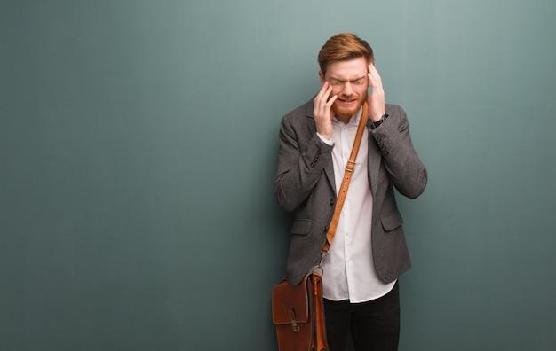 Молодой рыжий деловой человек отчаянно и грустно