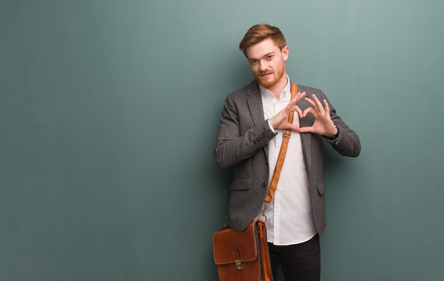 手でハートの形をしている若い赤毛のビジネスマン