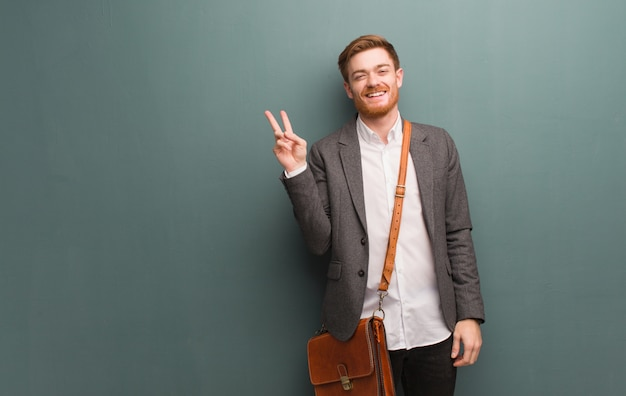 Young redhead business man doing a gesture of victory