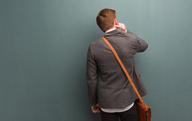 Young redhead business man from behind thinking about something
