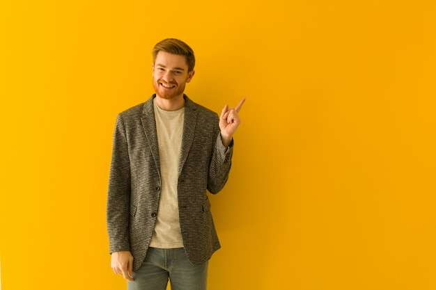 Young redhead business man pointing to the side with finger