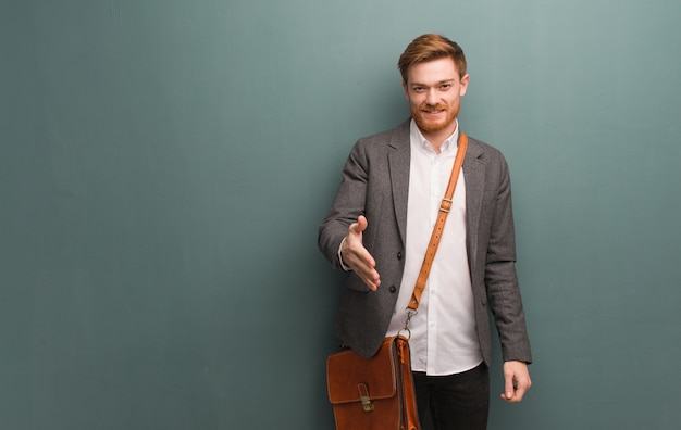 Young redhead business man reaching out to greet someone