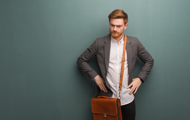 Young redhead business man scolding someone very angry