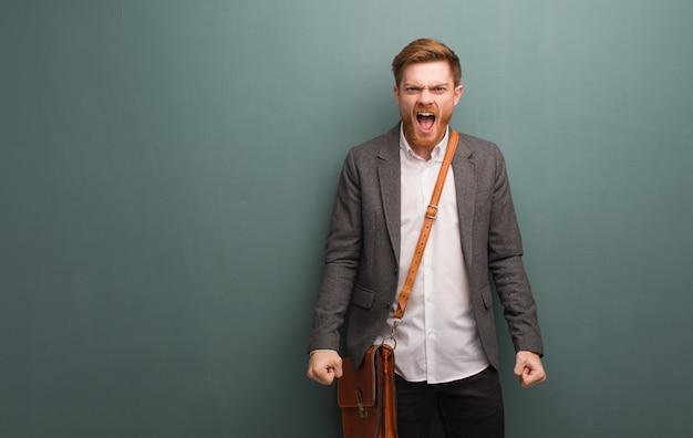 Молодой рыжий деловой человек кричит очень злой и агрессивный