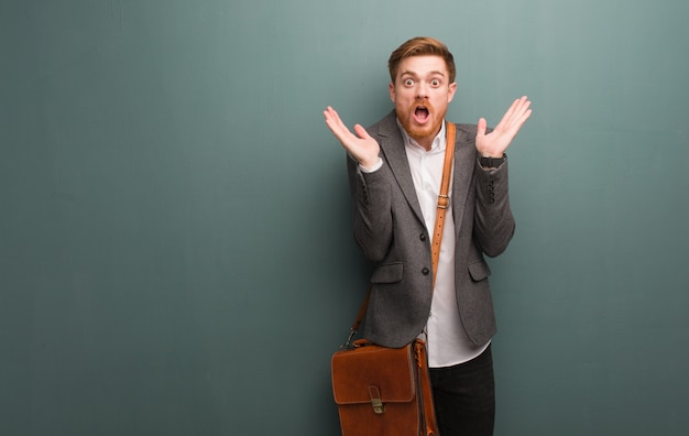 Young redhead business man surprised and shocked