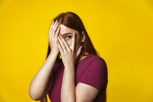 Young redhead caucasian girl is covering face with hands and looking through the fingers