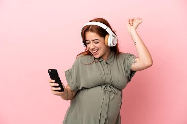 분홍색 배경에 고립 된 젊은 빨간 머리 백인 여자 임신과 음악을 들으면서 춤