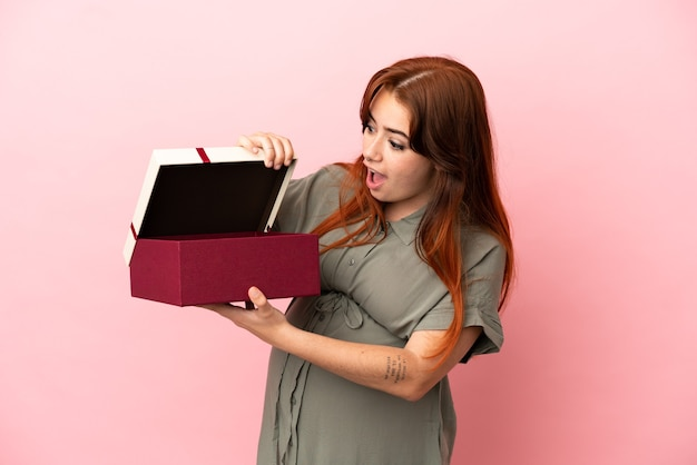 妊娠中のピンクの背景に分離され、驚きの表情で贈り物を保持している若い赤毛白人女性