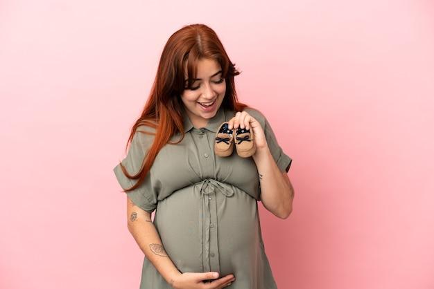 Молодая рыжая кавказская женщина изолирована на розовом фоне беременной и держит детские пинетки с удивленным выражением лица