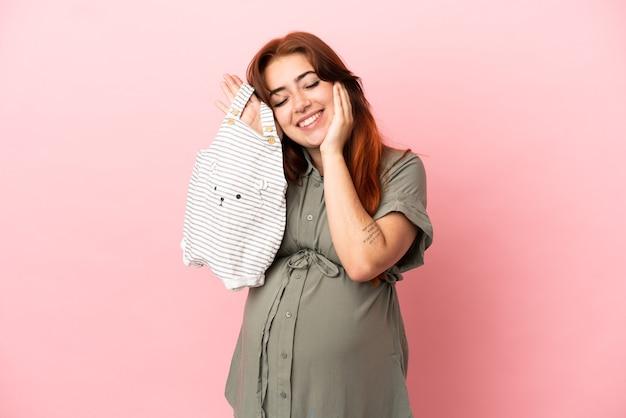 妊娠中のピンクの背景に分離され、赤ちゃんの服を保持している若い赤毛の白人女性