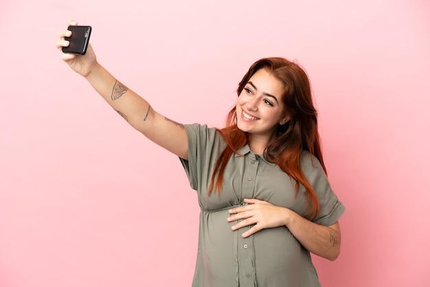 妊娠し、selfieを作るピンクの背景に分離された若い赤毛白人女性