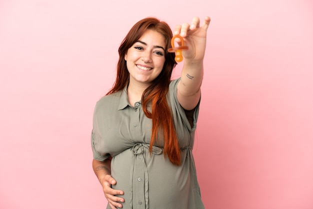 Young redhead caucasian woman isolated on pink background pregnant and holding a pacifier